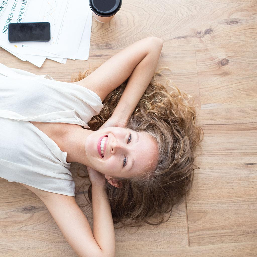 Symbolbild zu Bodenbelaege - junge Frau liegt glücklich auf einem Fussboden