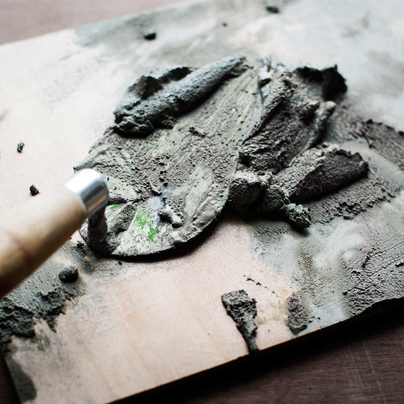 Zement im Einsatz auf Kelle und Holzbrett